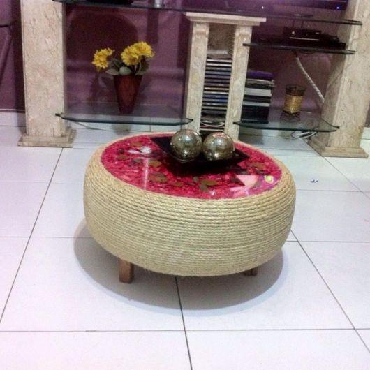 Mesa de centro de pneu com tampo vermelho.