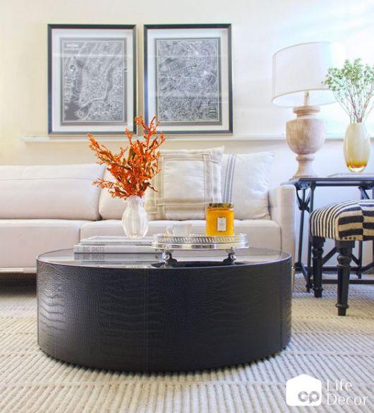 Mesa de centro redonda com enfeite laranja.