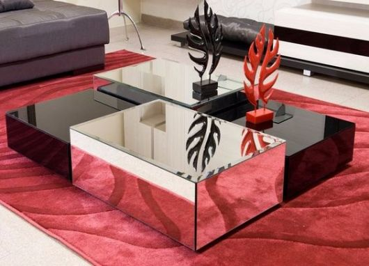 Mesa de centro preta com vidro espelhado.