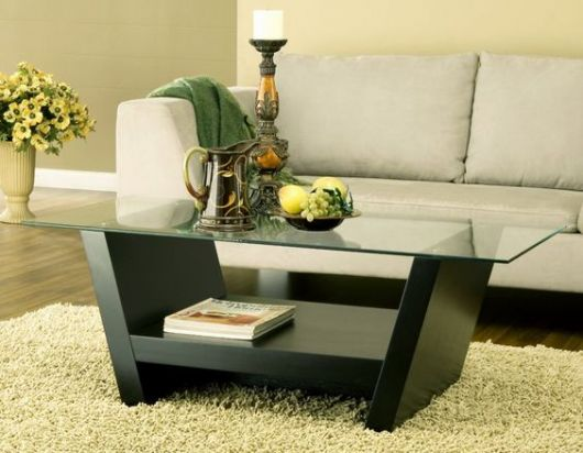 Mesa com suporte inferior na cor preta e parte superior de vidro.