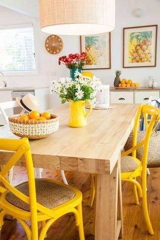 Cozinha com mesa de madeira e cadeiras amarelas.