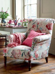 Poltrona florida com almofada rosa.