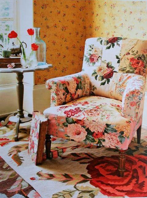 Poltrona florida em sala com decoração de estampas.
