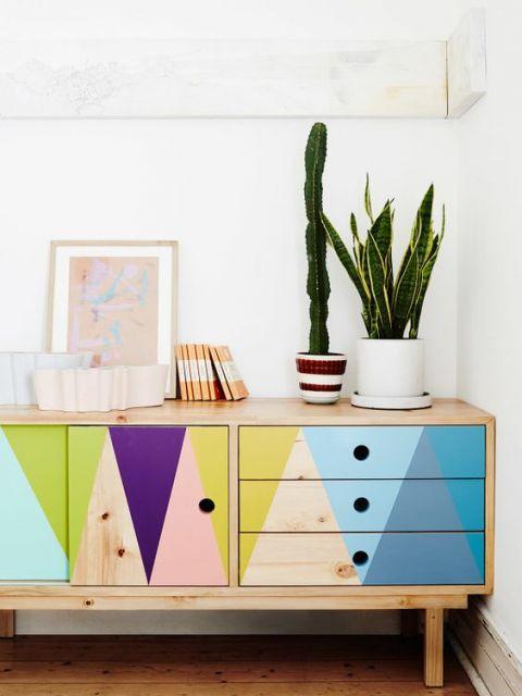 Quadro minimalista apoiado em cômoda colorida.
