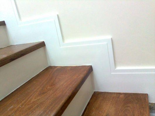 Rodapé de gesso que acompanha os degraus de uma escada com piso de madeira.