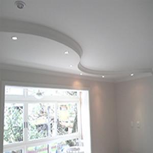 Rodapé de gesso para teto instalado de forma curvilínea com pequenas lâmpadas ao longo de sua extensão.