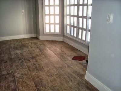 Ambiente vazio com grandes janelas, chão de madeira e um rodapé de gesso simples instalado em toda a sua extensão.