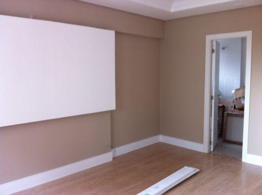Ambiente vazio com a porta aberta e um rodapé de gesso instalado na parte inferior da parede. O rodapé também contorna a porta.