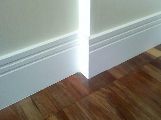 Rodapé de gesso simples com duas listras na parte inferior de uma parede com chão de madeira.