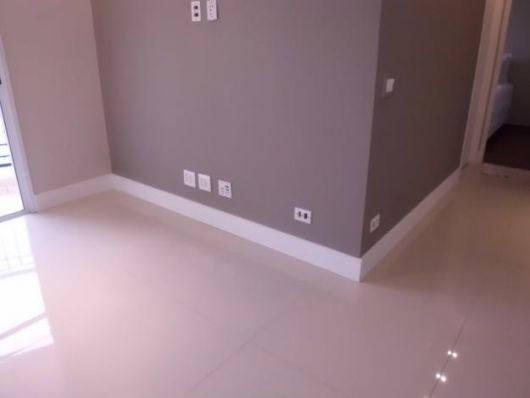 Rodapé de gesso na parte inferior de uma parede em uma sala vazia com chão de porcelanato.