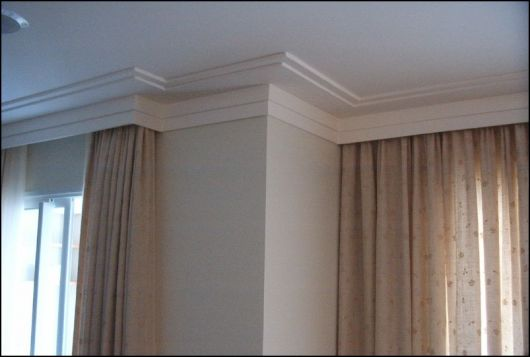 Rodapé de gesso para teto com poucos detalhes em um ambiente com muitas cortinas.
