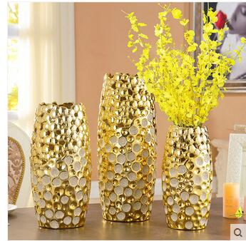 Vaso de cerâmica dourado e branco.