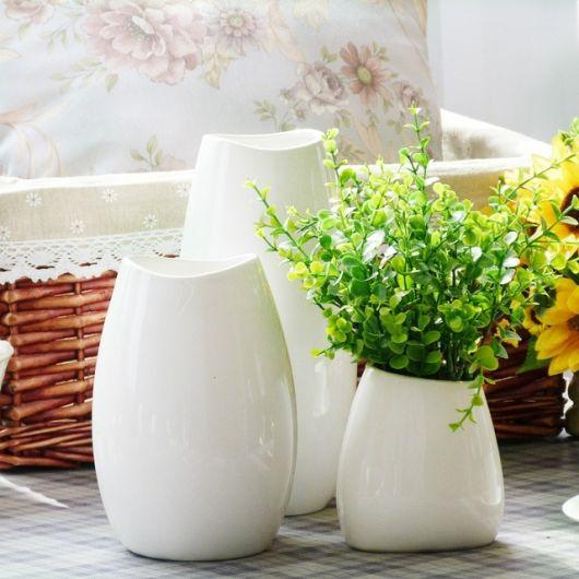 Vaso de cerâmica branco com plantinhas.
