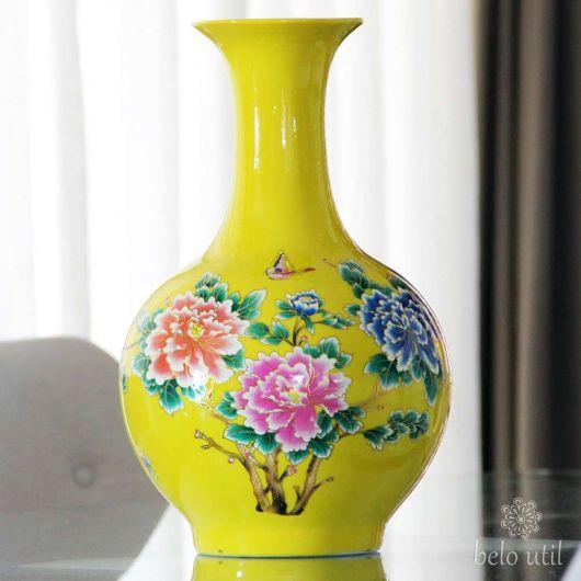 Vaso de cerâmica amarelo com detalhes florais.