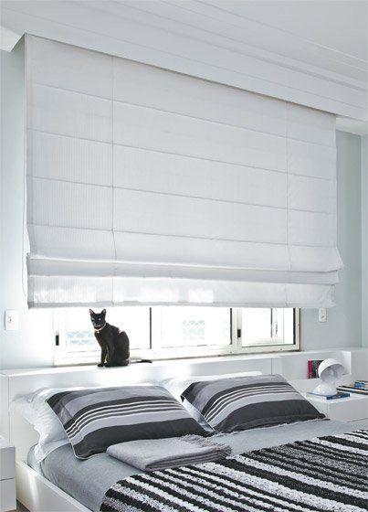 Quarto com blecaute branco e gato na frente da janela.
