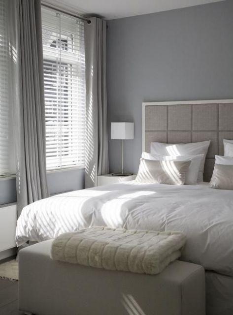 Cortina cinza em quarto de casal com roupa de cama branca.