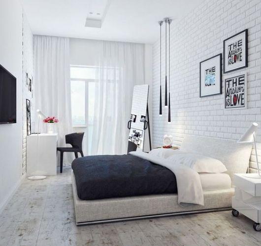 Quarto branco, com quadros, luminária e espelho de chão.