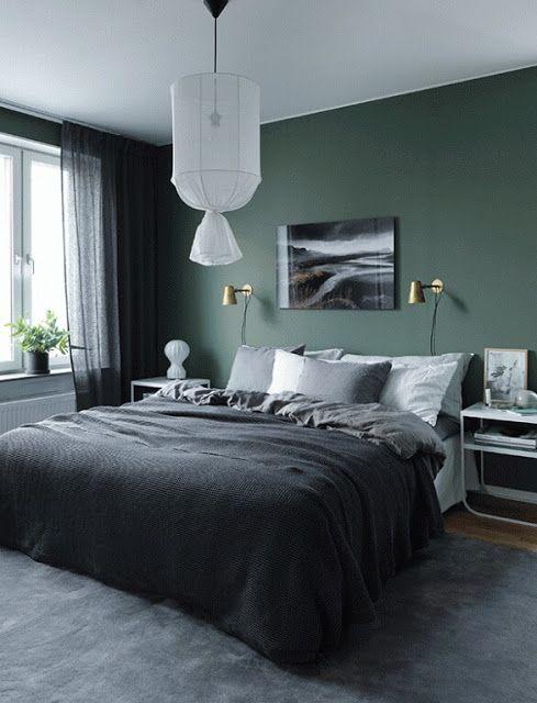 Quarto com parede verde, roupa de cama, tapete e cortina escura.