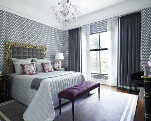 Quarto com papel de parede estampado, móvei bordo e roupa de cama branca.