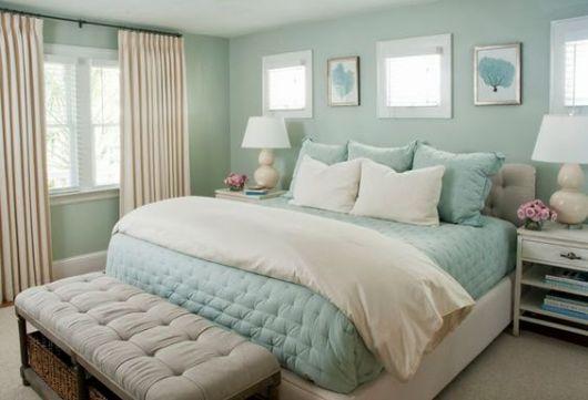 Quarto com paredes verdes, roupa de cama azul e cortina clara.