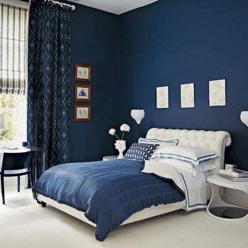Quarto com roupa de cama, paredes e cortina azul.