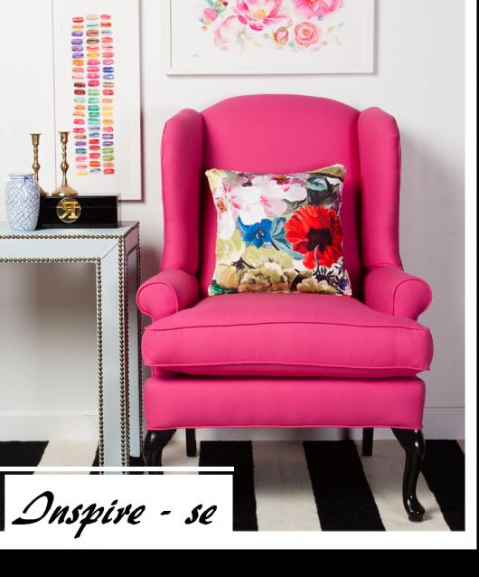 Poltrona cor de rosa com almofada estampada em sala com piso preto e branco.