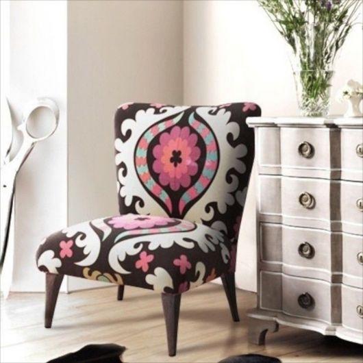 Poltrona estampada nas cores, branco, marrom e rosa.