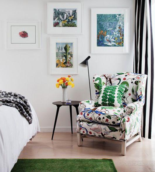 Poltrona estampada em quarto clean branco com quadrinho decorativos.