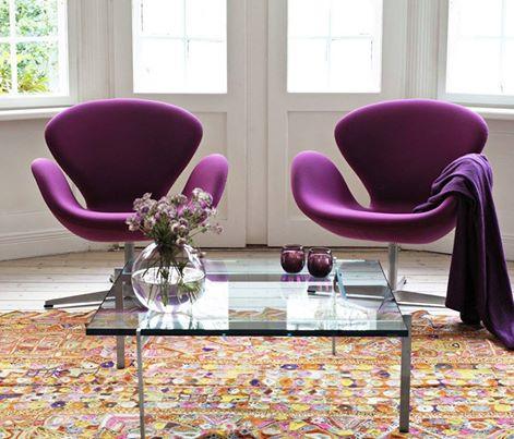 Poltronas na cor roxa, giratórias em sala com mesa de centro de vidro e paredes brancas.