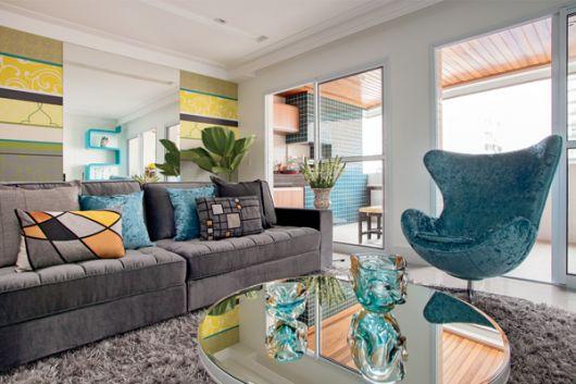 Sala com sofá cinza, almofadas colorida, tapete cinza e mesa de centro em vidro.