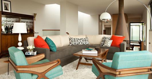 Sala clean com sofá amplo tons nude e poltronas azul turquesa combinando com as cores das almofadas.