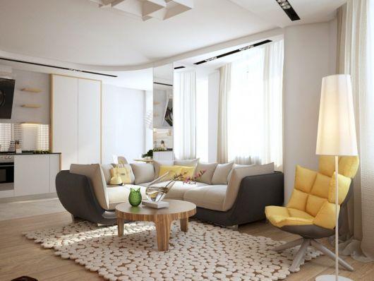 Sala clean com sofá nude, tapete nude e mesa de centro de madeira com poltrona amarela estofada confortavel.