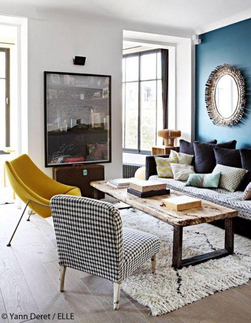 Sala moderna com poltronas amarela e preta e branca, com sofa de almofadas e paredes azuis.