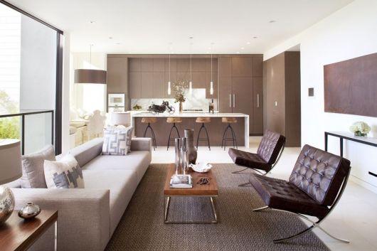 Sala clean com sofa branco e poltronas marrom de corino.