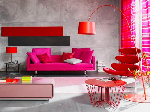 Sala com sofá rosa, paredes cinza, poltrona design diferente e mesa de centro rosa claro.