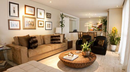 Sala coclean com sofa bege e poltronas marrom monocromaticas.