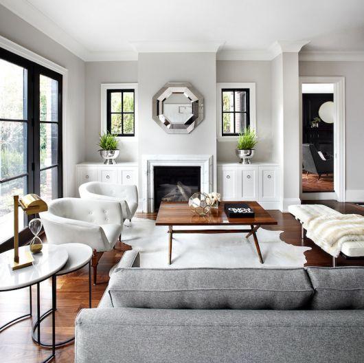 Sala branca com janelas amplas, sofa cinza e poltronas pé de madeira branca.