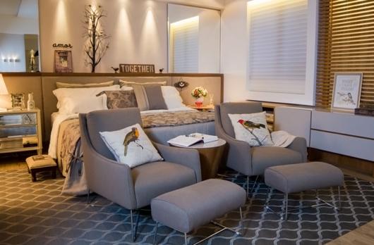 Modelo de quarto branco com espelhos, cama branca e poltronas cinza estofadas.