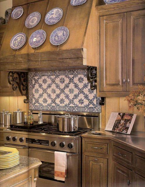 Cozinha com móveis de madeira e um quadrante revestido com azulejos portugueses entre o fogão e o armário. No armários de madeira estão posicionados pratos com decoração semelhante à dos azulejos.