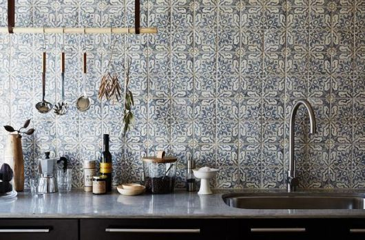 Bancada da pia em frente a uma parede revestida completamente com azulejos portugueses baseados em formas geométricas.