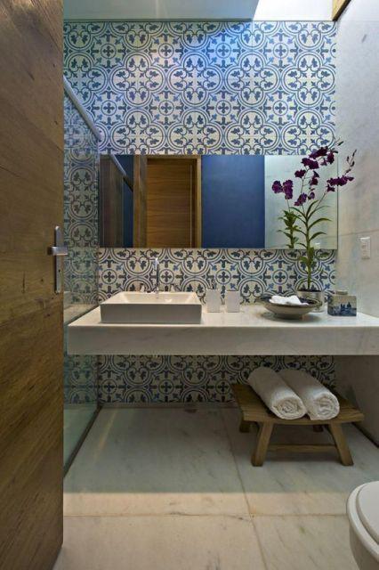 Parede de um banheiro com azulejos portugueses atrás de uma bancada com um grande espelho posicionado nela.