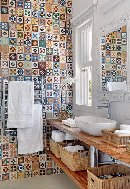 Parede de banheiro ao lado da bancada completamente revestida com azulejos portugueses coloridos.