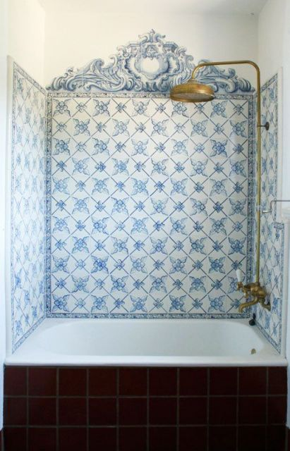 Três paredes que envolvem uma banheira revestidas com azulejos portugueses.
