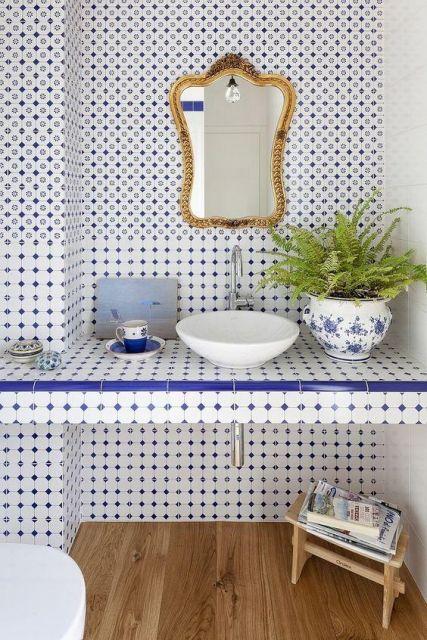 Revestimento tanto da bancada quanto da parede um banheiro completamente revestida com azulejos portugueses baseados em uma linha mais minimalista. com pequenos pontos.