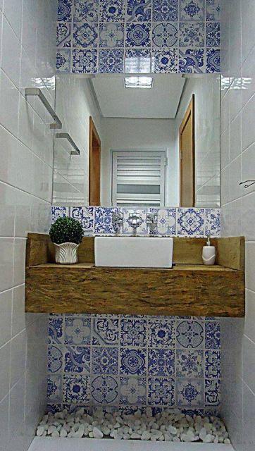 Bancada de madeira de um lavabo com espelho em frente a uma parede alta revestida com azulejos portugueses.
