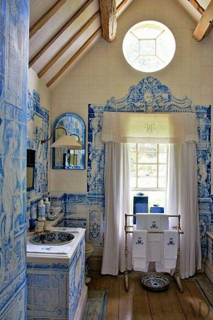 Todas as paredes de um banheiro revestidas com azulejos portugueses muito detalhados que juntos formam pinturas.