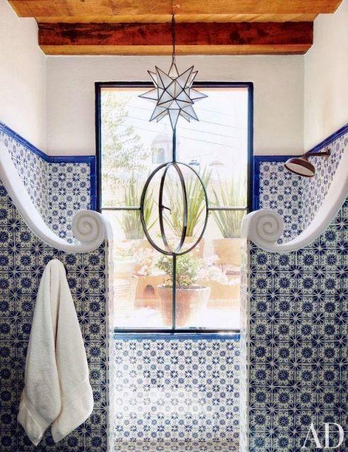 Paredes do banheiro com uma janela entre elas. As duas são revestidas com azulejos portugueses.