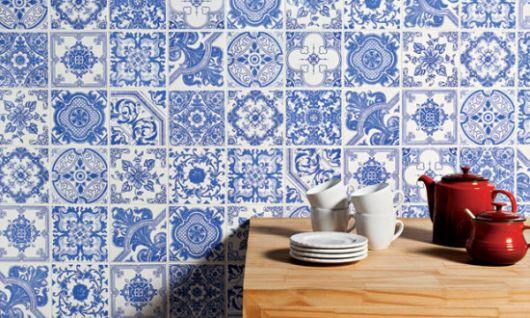 Parede revestida com azulejos portugueses e parte de uma bancada na frente com algumas louças acima dela.