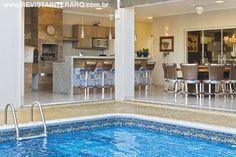 Piscina integrada à área de churrasqueira. Tanto na piscina quanto na bancada da churrasqueira existem azulejos portugueses.