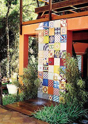 Área verde de um jardim. O chuveiro tem uma parede revestida com azulejos portugueses diferentes feitos a partir de diversas cores.